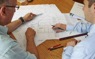 Two men looking at building design plans. Local authority building control (LABC)